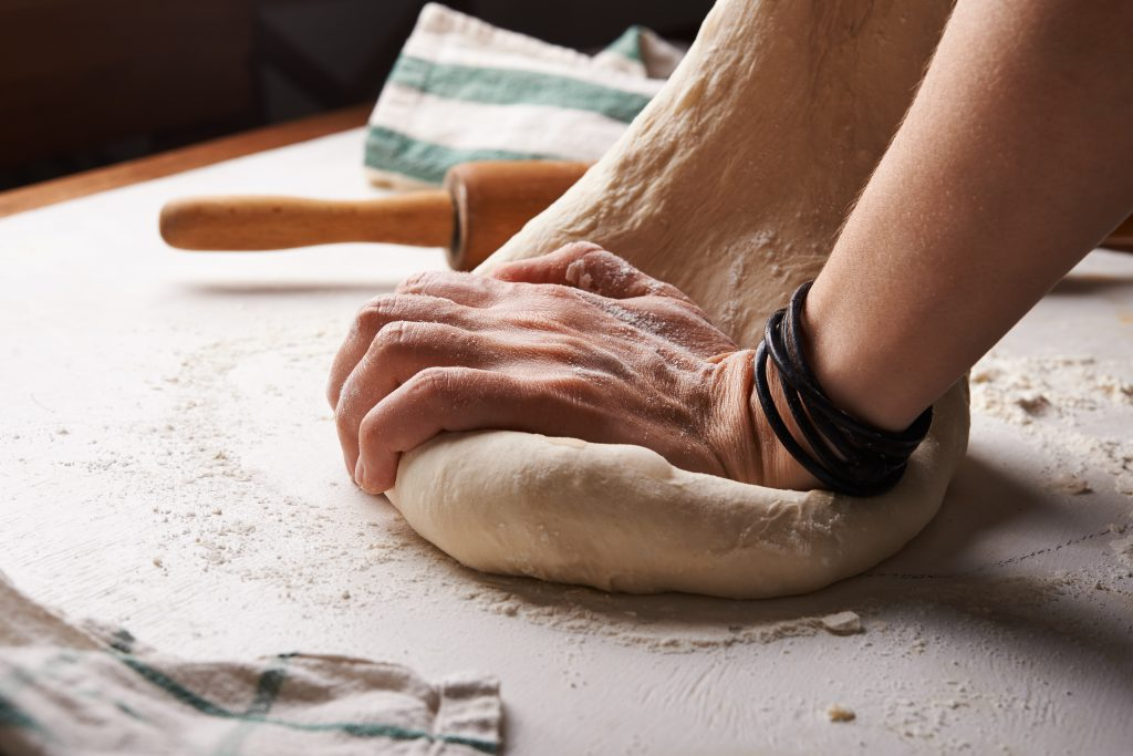 An image of a person kneading and pulling at bread dough.