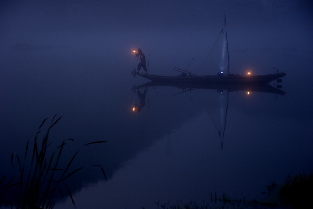 A man on boat on dark water.