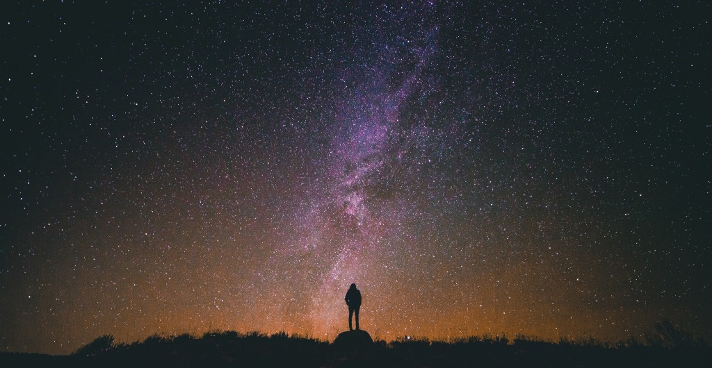 An image of a person standing alone before an impressive night sky. Not really about doing, a devotional about Philippians 4, verses 11-14.