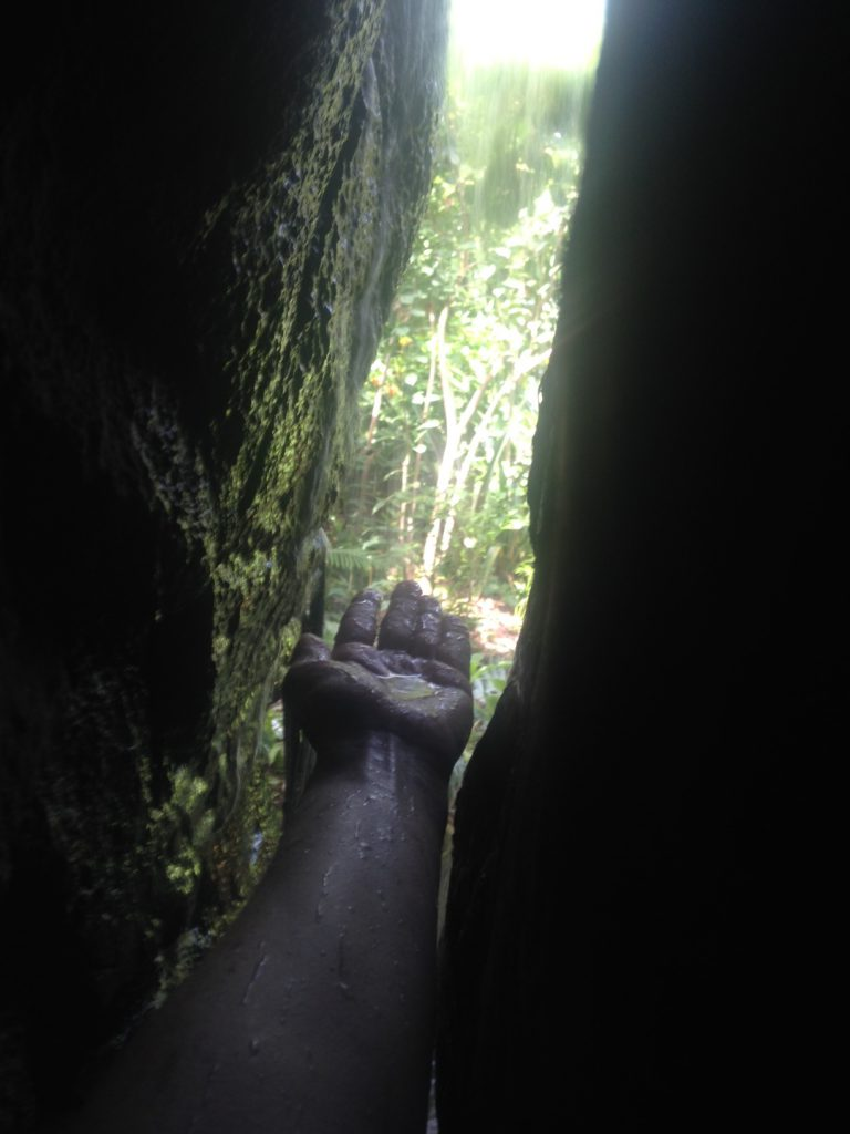 my hand, reaching through a crack in a rock towards a waterfall