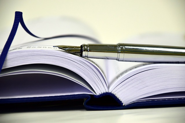 a fountain pen sits atop an open notebook
