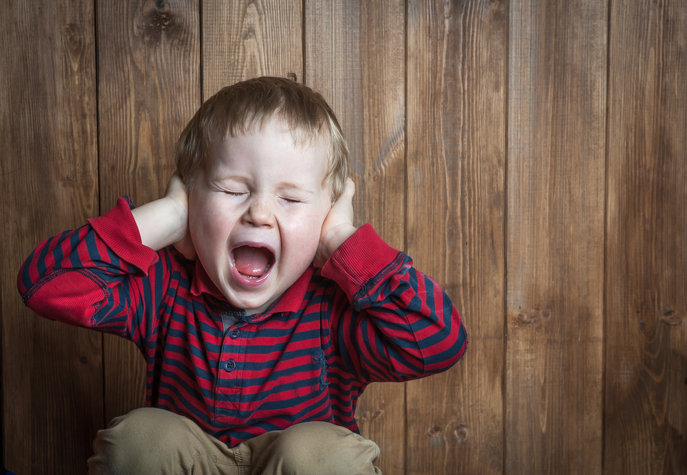 a toddler boy is yelling and has his hands over his ears
