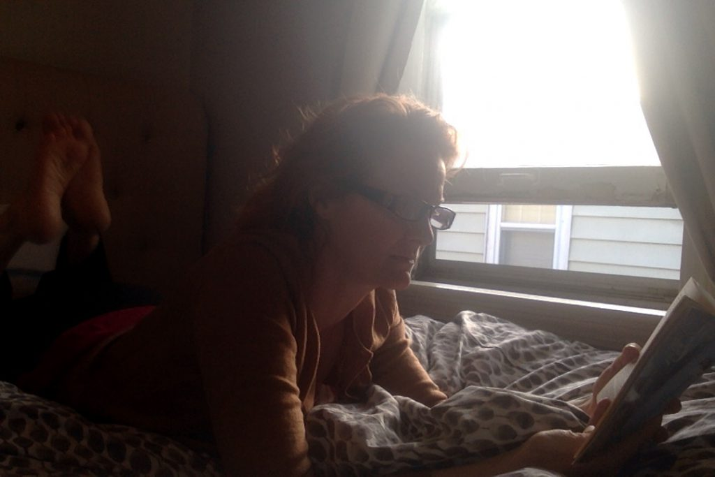 a picture of me, on my stomach on my bed, right next to an open window, reading