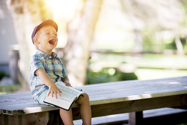 An image of a kid with a Bible on his lap, laughing. This image is in honor of the rather bad pun at the end of our second psalm.