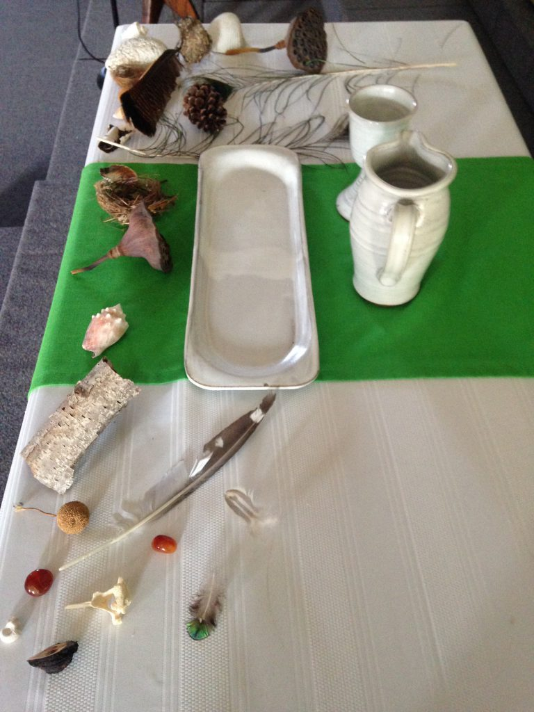 Shells, rocks, feathers, nuts, animal bones, and nests are displayed on a table set for communion.