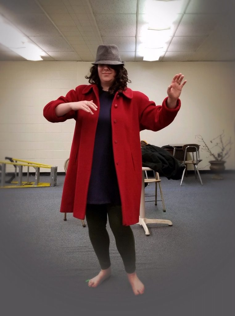 Photo of a woman with brown curly hair wearing a red coat and a fedora, dancing by herself.