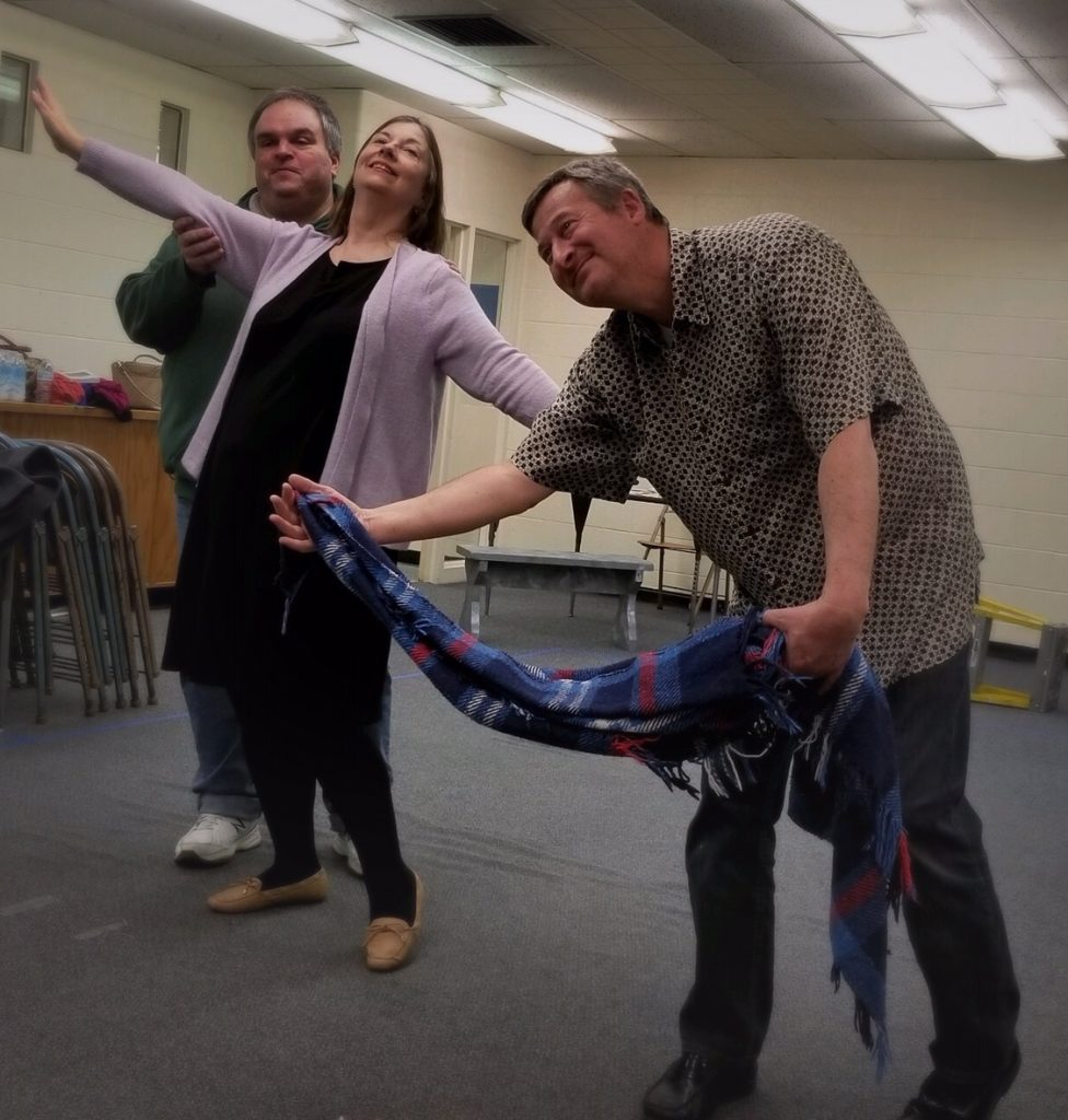 Photo of three people rehearsing a play. A man stands behind a woman, she has her arms spread wide and she is smiling. Another man is dancing with a blanket as if it is his partner.
